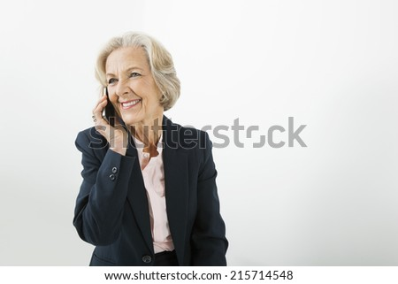 Senior businesswoman using cell phone in office - stock photo