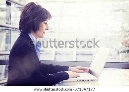 Senior businesswoman with laptop at office, working, Large copyspace.
