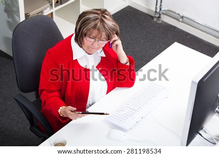 senior businesswoman working with a tablet and using a phone - stock photo