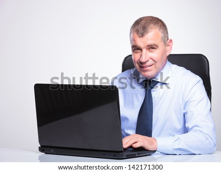 senior bussines man at desk working on his laptop while smiling at the camera. on gray background