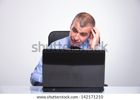 senior bussines man sitting at desk and looking at the laptop questioningly or bored.on gray background