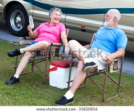 Senior campers sitting in folding chairs outside their motor home. - stock photo