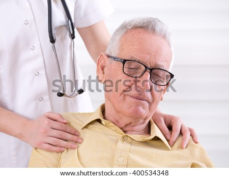 Senior care concept. Young nurse holding hands on shoulders of old smiling man - stock photo