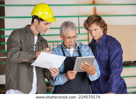 Senior carpenter holding tablet computer while communicating with colleagues in workshop - stock photo