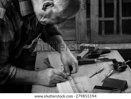 Senior carpenter marking a measurement on a wooden plank - stock photo