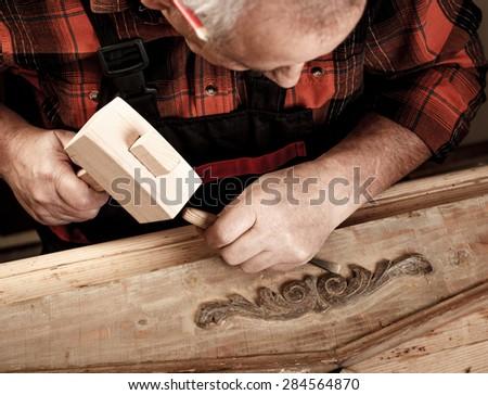 Senior carpenter restoring old furniture in his workshop - stock photo