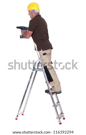 Senior carpenter stood up ladder with drill - stock photo