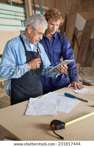 Senior carpenter using digital tablet with coworker in workshop - stock photo