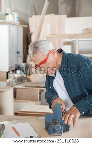 Senior carpenter using electric planer while wearing protective glasses in workshop - stock photo