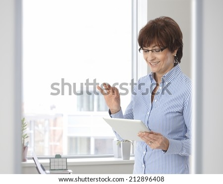 Senior casual businesswoman with tablet computer at business office. Standing, smiling, looking at screen, wearing glasses, gesturing. - stock photo