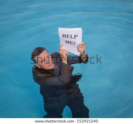 Senior caucasian businessman in suit up to neck in deep blue water worried about drowning in paperwork and holding help me document - stock photo