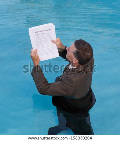 Senior caucasian businessman in suit up to waist in deep blue water worried about being underwater with mortgage payments - stock photo