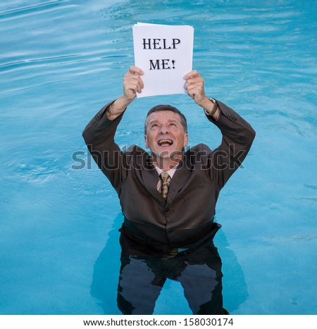 Senior caucasian businessman in suit up to waist in deep blue water worried about drowning in paperwork and holding help me document - stock photo