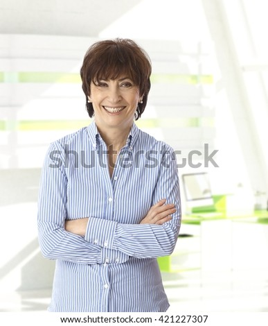 Senior caucasian casual businesswoman standing with arms crossed at bright office. Smiling, looking at camera, copyspace.