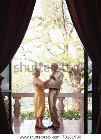 senior caucasian couple on vacation, dancing on terrace in hotel. Vertical shape, full length, side view - stock photo