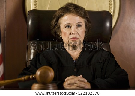 Senior Caucasian judge sitting in courtroom with mallet on table - stock photo