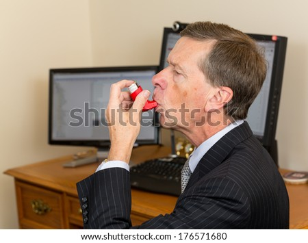 Senior caucasian man  in suit at desk with computer screens with asthma inhaler to handle problems with breathing - stock photo