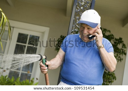 Senior Caucasian man watering plants while enjoying a chat on cellphone - stock photo