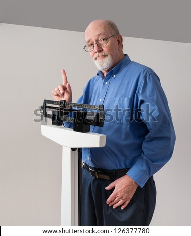 Senior caucasian man weighing himself on vertical weight scale. He looks thoughtful and concerned. - stock photo