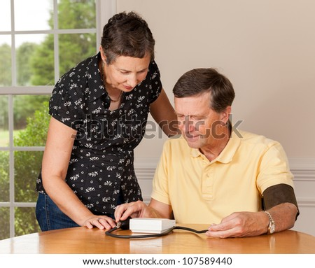 Senior caucasian retired male taking blood pressure at home - stock photo