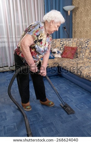 Senior caucasian woman about ninety years old runs vacuum cleaner, She cleans blue carpet in her room - stock photo