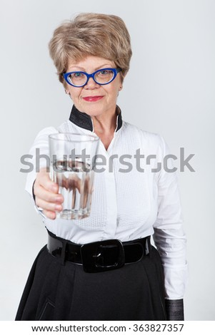 Senior Caucasian woman stretching hand with clear water in transparent glass