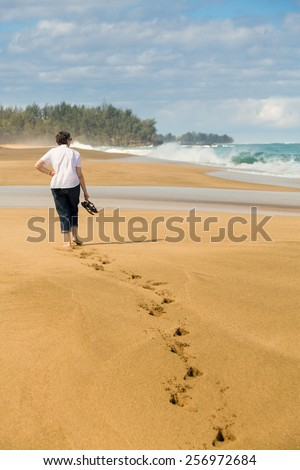 Senior caucasian woman walks down sandy Lumahai beach on Kauai Hawaii - stock photo