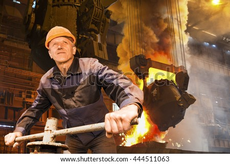 Senior Caucasian worker in a hardhat is in the ironworks with melting steel on background