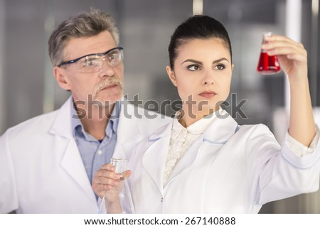 Senior chemistry professor and his assistant looking on flask with red fluid  in  laboratory. - stock photo