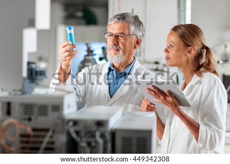 Senior chemistry professor/doctor in a lab with his female colleague carrying out research experiments (color toned image; shallow DOF)