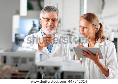 Senior chemistry professor/doctor in a lab with his female colleague carrying out research experiments (color toned image; shallow DOF) - stock photo