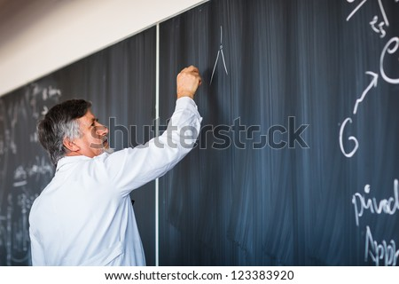 Senior chemistry professor writing on the board while having a chalk and blackboard lecture (shallow DOF; color toned image) - stock photo