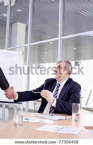 Senior chief shaking hands with his partner - stock photo