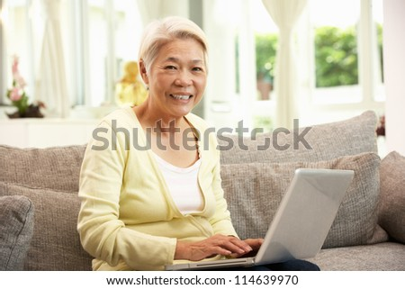 Senior Chinese Woman Using Laptop Whilst Relaxing On Sofa At Home