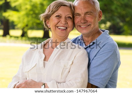 Senior citizen couple laughing at camera outdoors - stock photo