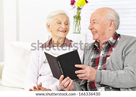 Senior citizen couple reading a book in a retirement home - stock photo