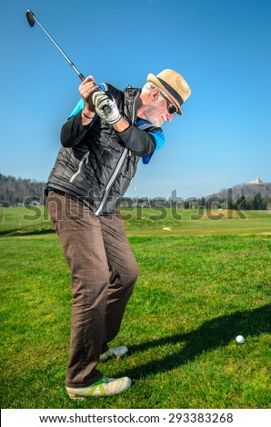 Senior citizen is playing golf. Active retirement. A man is golfing to stay in shape. On green grass with woods in the background - stock photo