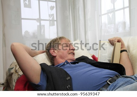 senior citizen is reading a book on a sofa