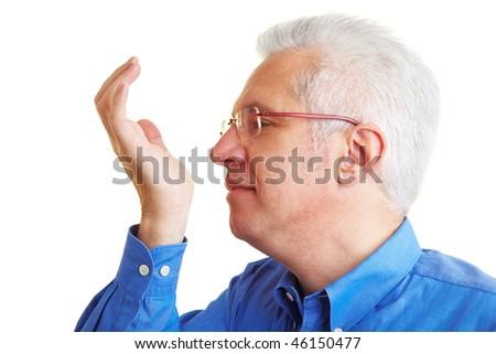 Senior citizen smelling perfume on his hand pulse - stock photo