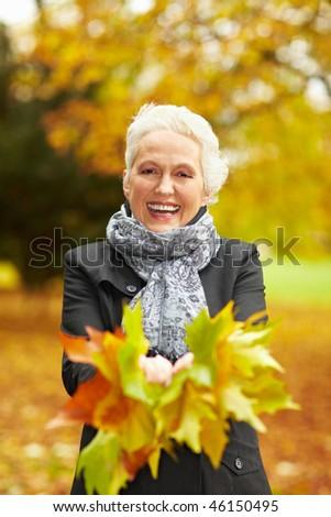 Senior citizen stroll in a park in autumn - stock photo