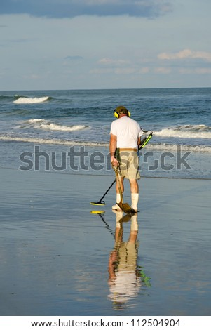Senior citizen with the metal detector during the beach treasure hunt
