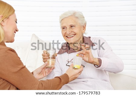 Senior citizen woman getting medical pill with water in a retirement home