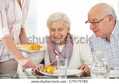 Senior citizens couple eating lunch at nursing home - stock photo