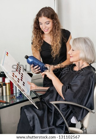 Senior client and hairdresser choosing hair color at beauty salon
