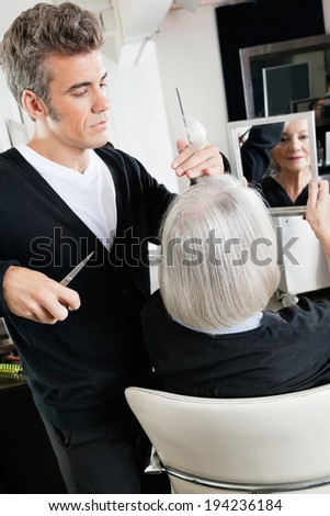 Senior client holding mirror while male hairstylist cutting her hair at beauty salon