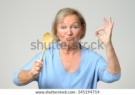 Senior cook or housewife showing her approval of a recipe as she holds a wooden spoon in one hand while making a perfect gesture with the other, over grey - stock photo