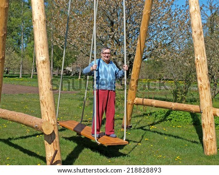 Senior country farmer swinging on big wooden swings