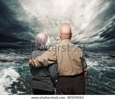 Senior coupel looking at storm - stock photo