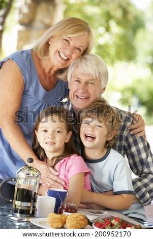 Senior couple and grandchildren eating breakfast outdoors - stock photo