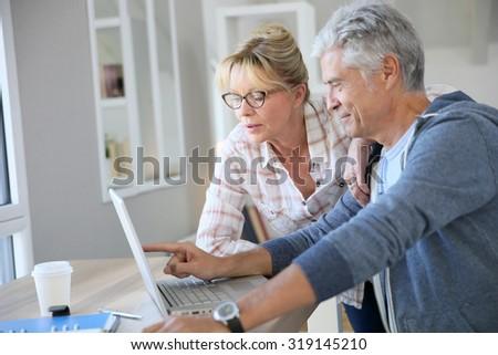 Senior couple at home checking expenses on internet - stock photo